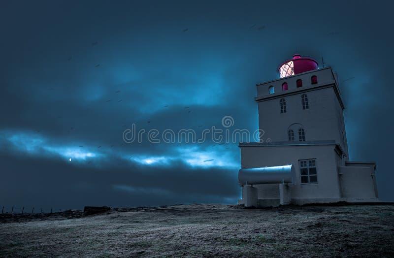Dyrholahey Lighthouse in Southern Iceland. Light shining out of the Dyrholahey Lighthouse just before sunrise in Vik, southern Iceland royalty free stock photos