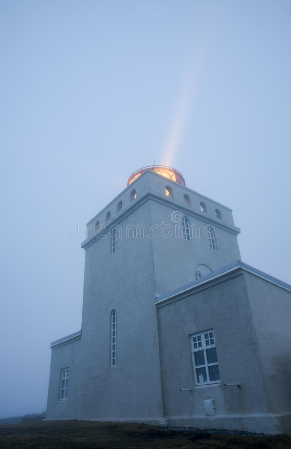 Dyrholahey Lighthouse in Southern Iceland. Light shining out of the Dyrholahey Lighthouse just before sunrise in Vik, southern Iceland royalty free stock images