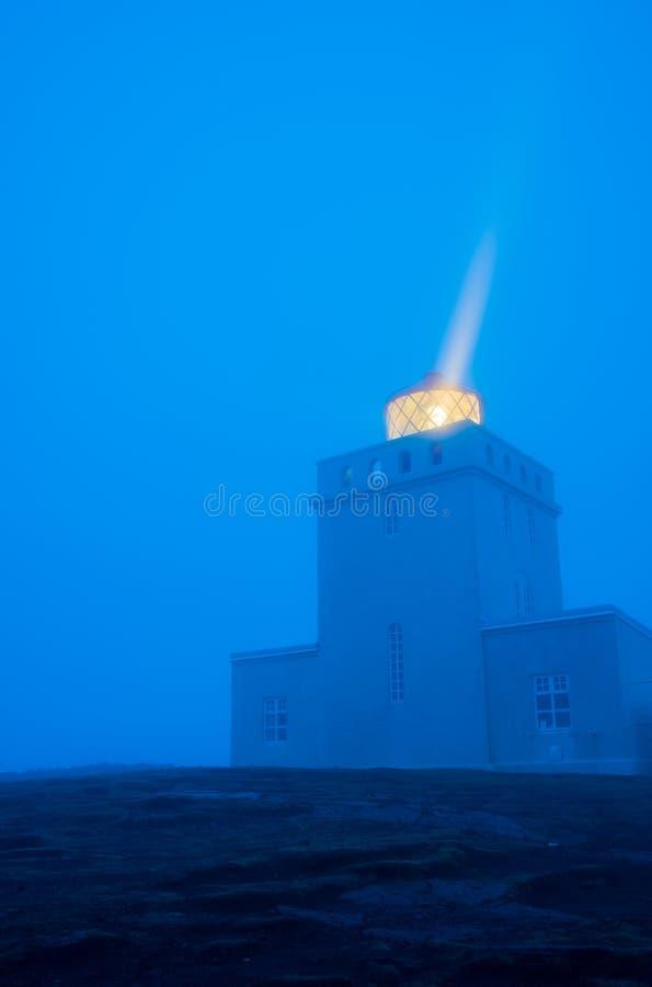Dyrholahey Lighthouse in Southern Iceland. Light shining out of the Dyrholahey Lighthouse just before sunrise in Vik, southern Iceland stock photography