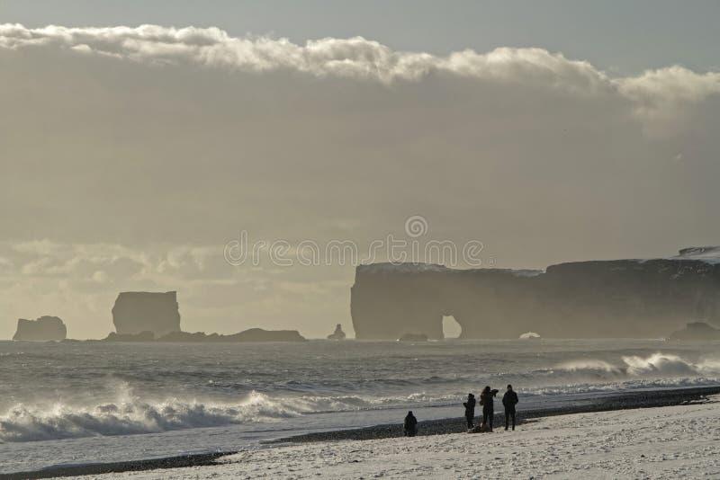 Dyrolaey y gente en la playa imagenes de archivo