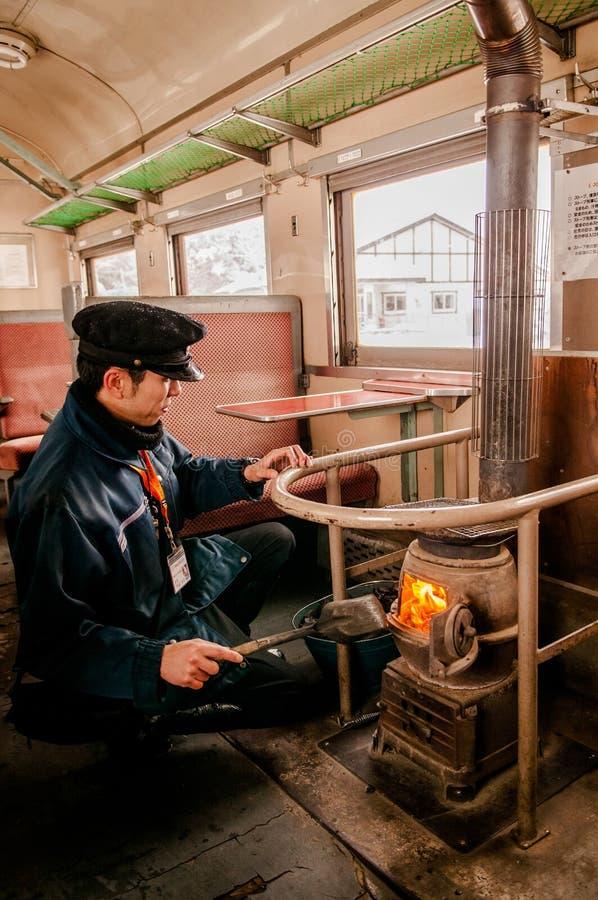 Dyrygent stawia węgiel w potbelly kuchence na starym rocznika pociągu Tsu obrazy royalty free