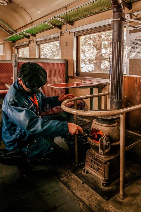 Dyrygent stawia węgiel w potbelly kuchence na starym rocznika pociągu Tsu fotografia stock