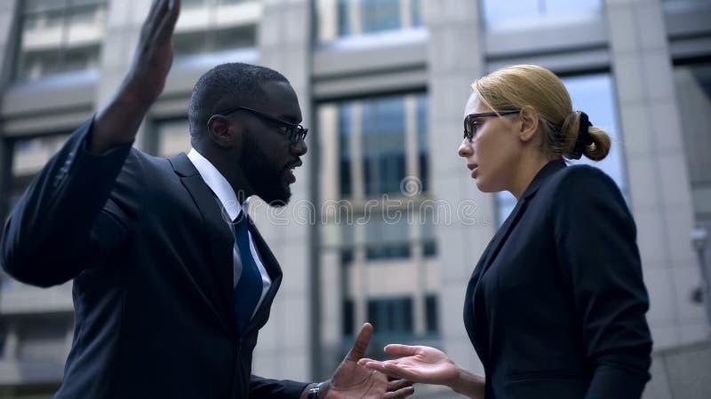 Dyryguje próbować uderzać żeńskiego urzędnika i dyskryminacja płaci, rasowy, nadużycie zdjęcia royalty free