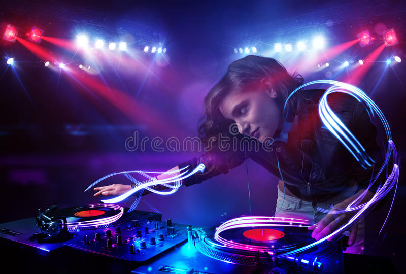 Dyskdżokej dziewczyna bawić się muzykę z lekkiego promienia skutkami na scenie zdjęcia stock