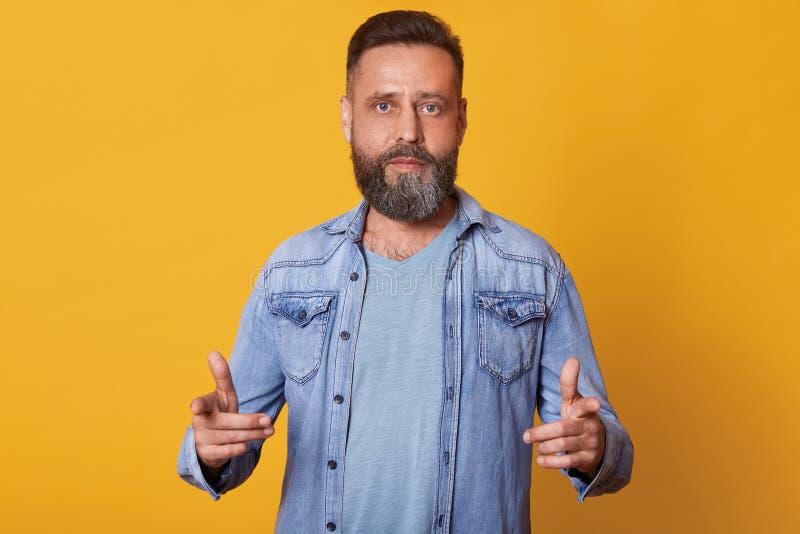 Dyskretny przystojny brodaty mężczyzna weaing bławą t koszula, cajg kurtka, pokazuje kierunek przed on z dwa forefingers fotografia stock