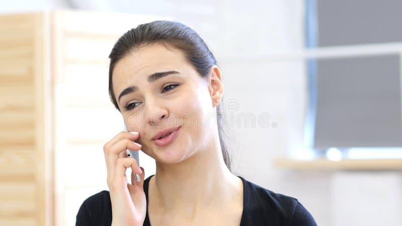 Dyskusja, kobieta Opowiada na telefonie w Jej biurze fotografia royalty free