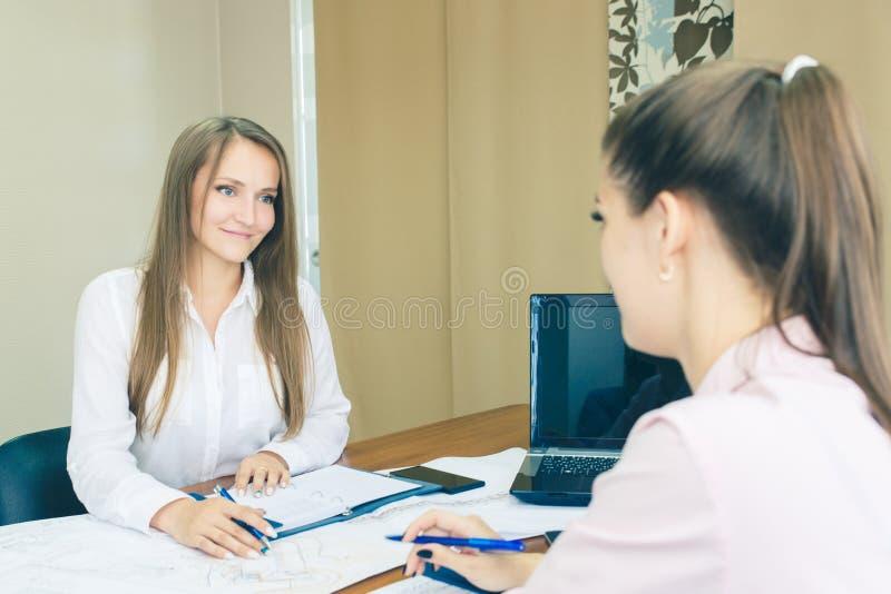 Dyskusja projekt w biurze Architekci z rysunkami w biurowym planowaniu pracują Dziewczyny w biurze fotografia stock