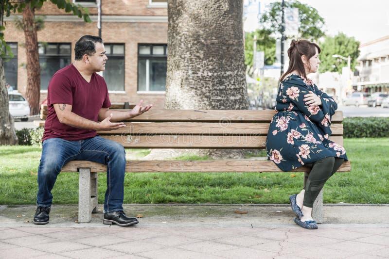Dyskutować Mieszającego Biegowej pary Siedzącego obszycie Zdala od Each Inny na Parkowej ławce zdjęcie royalty free