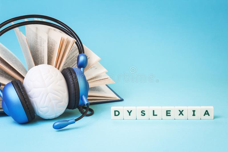 Dysleksji słowo z otwartą książką i hełmofonami fotografia royalty free