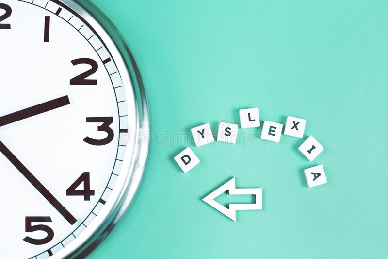 Dyslexia and read words with a big clock. Dyslexia and read words with a big analogue clock on mint background, reading difficulty and disorder concept royalty free stock photography