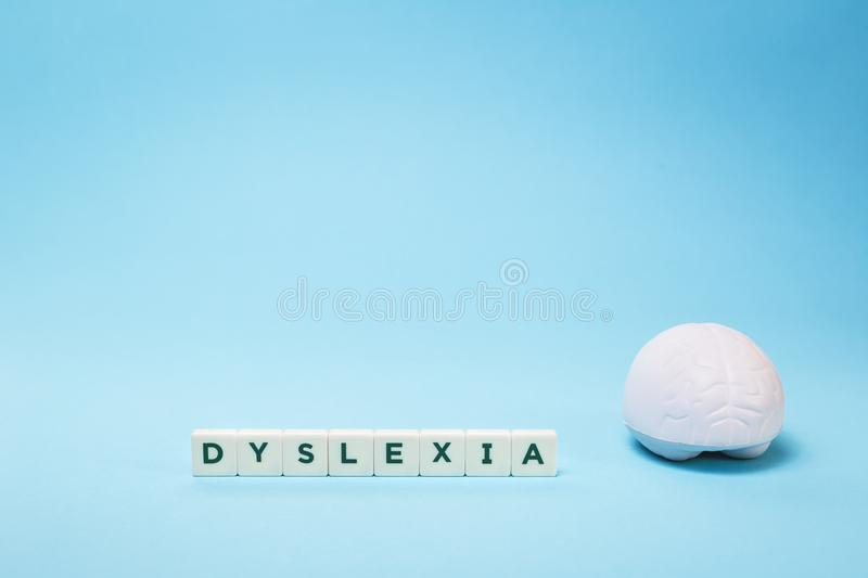 Dyslexia word with a brain on blue with copy space stock photography