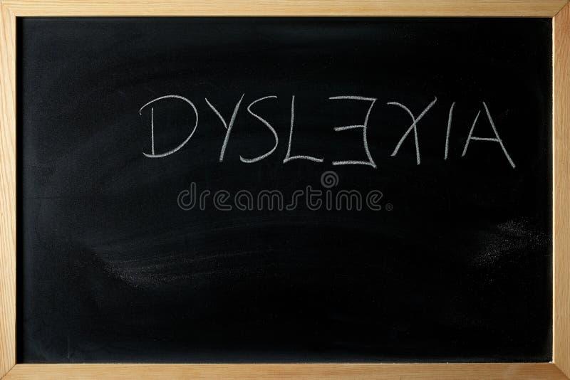 Dyslexiordet är skriftligt på en svart tavla arkivbild