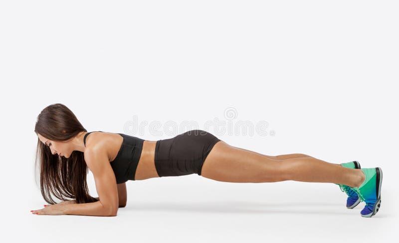 Dysponowana dziewczyna robi deski ćwiczeniu Sprawności fizycznej kobieta robi deski ćwiczeniu zdjęcie royalty free