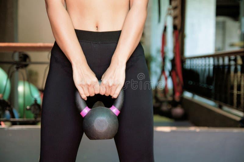 Dysponowana dziewczyna w sportów dźwignięć ciężarze robi sedna ćwiczy w gym obraz stock