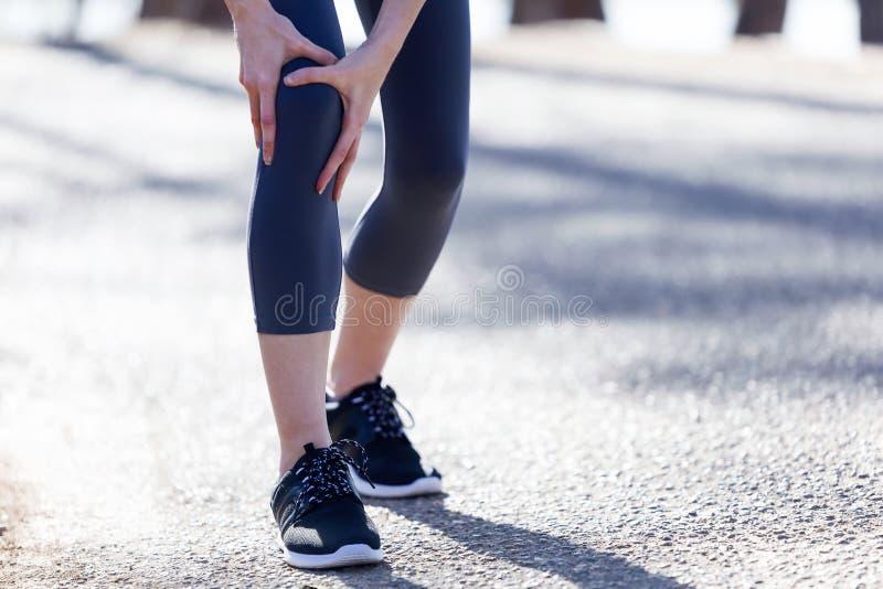 Dysponowana i sporty młoda kobieta z noga bólem w lesie obrazy stock