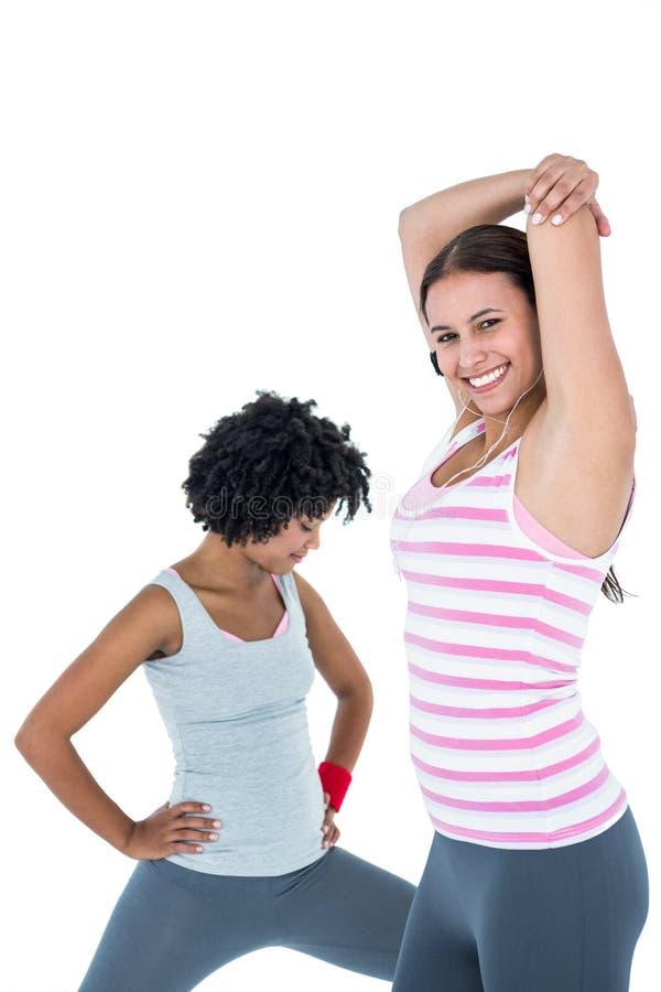 Dysponowana kobieta ćwiczy podczas gdy żeński przyjaciela rozciąganie zdjęcie stock