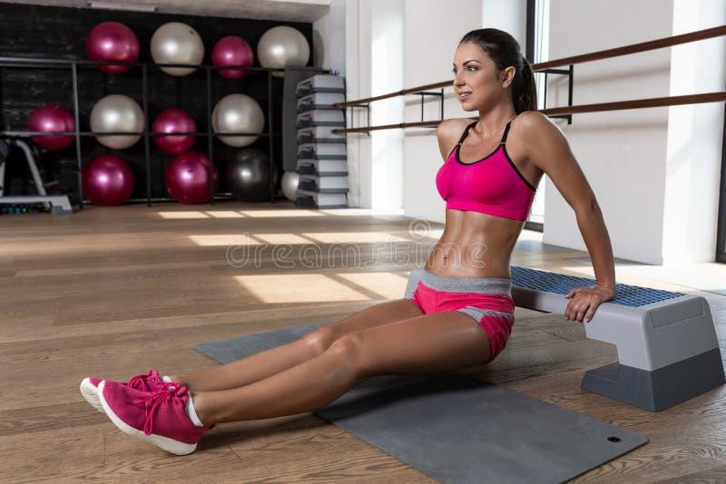 Dysponowana kobieta ćwiczy trening ręk ćwiczenia stażowego triceps i bicepsy out podnosi robić pcha fotografia stock