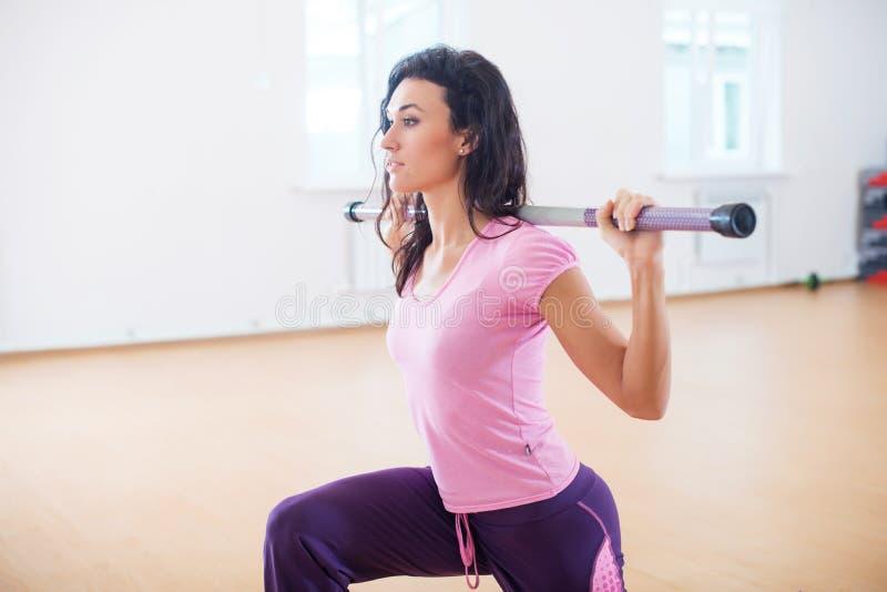 Dysponowana kobieta ćwiczy w sprawność fizyczna klubie robi lunge kuca z barbell na ona ramiona obrazy royalty free
