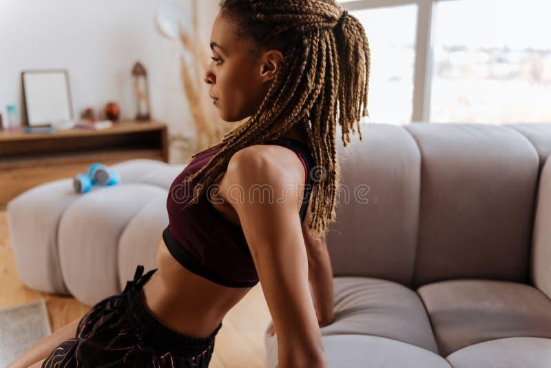 Dysponowana kobieta jest ubranym krótko sporta wierzchołek ćwiczy w domu fotografia stock