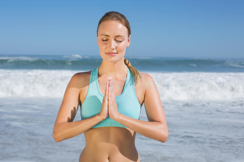 Dysponowana kobieta medytuje na plaży obrazy royalty free