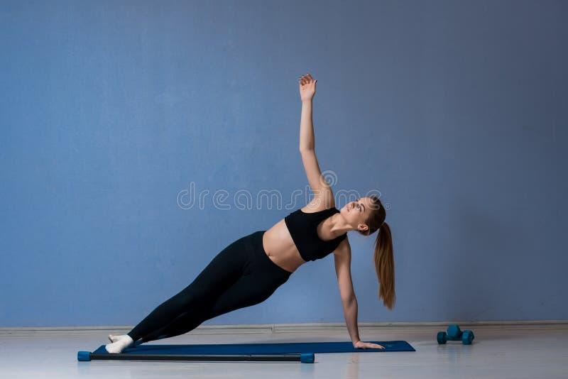 Dysponowana kobieta robi bocznej deski joga pozie na macie fotografia royalty free