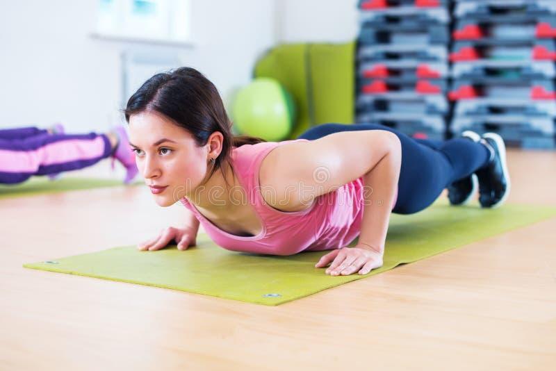 Dysponowana kobieta robi deski ćwiczeniu i pcha podnosi działanie na brzusznych mięśni triceps zdjęcie stock