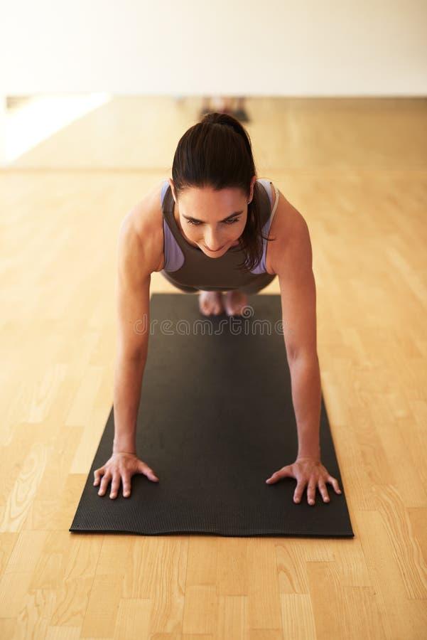 Dysponowana kobieta robi prasy podnosi w gym zdjęcie stock