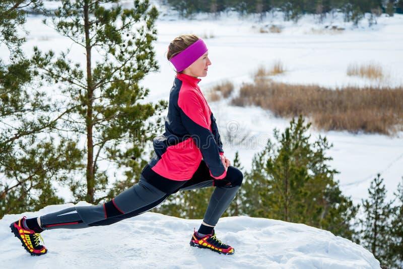 Dysponowana kobieta robi rozciąganiu ćwiczy przed biegać outdoors Zimy ulicy szkolenie zdjęcia stock