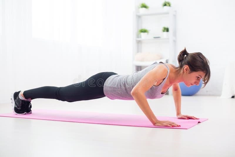 Dysponowana kobieta robi Ups na podłoga w jej żywym pokoju w domu ćwiczenie mata fotografia stock