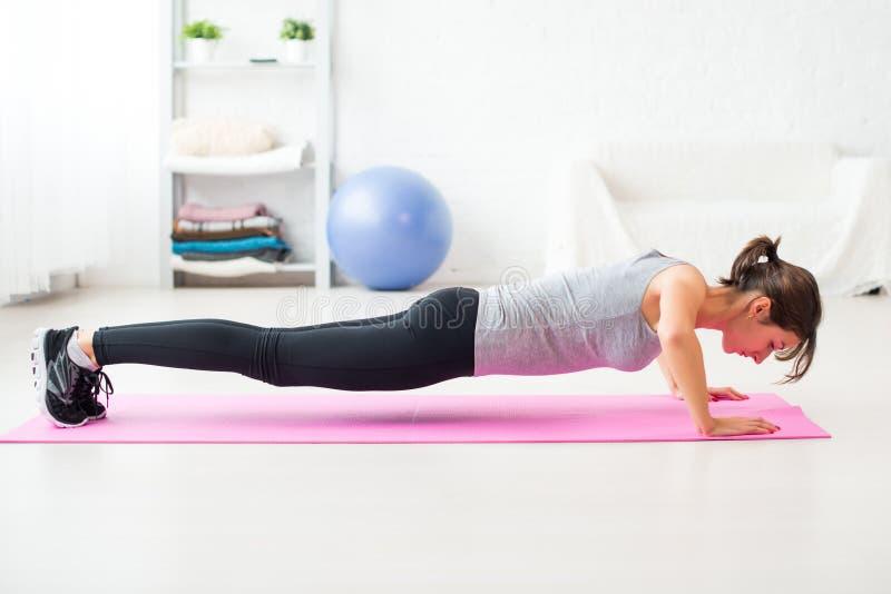 Dysponowana kobieta robi Ups na podłoga w jej żywym pokoju w domu ćwiczenie mata obraz royalty free