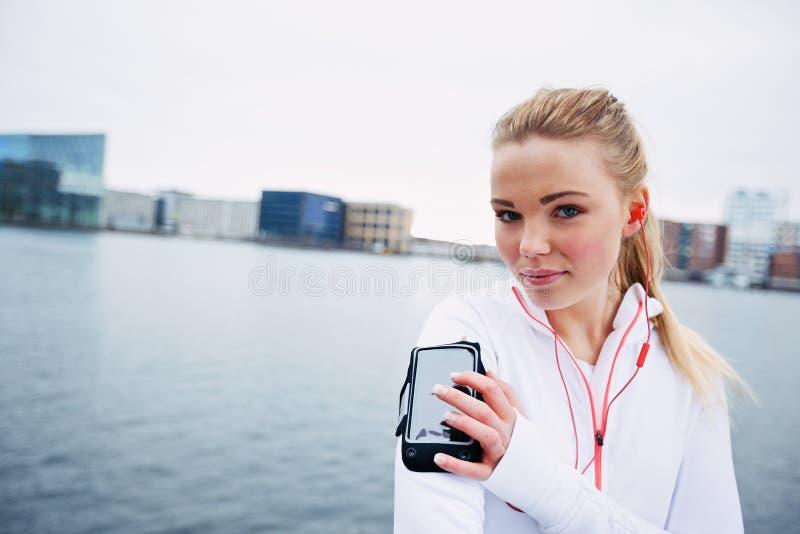 Dysponowana młoda dama monitoruje jej postęp na smartphone obraz stock