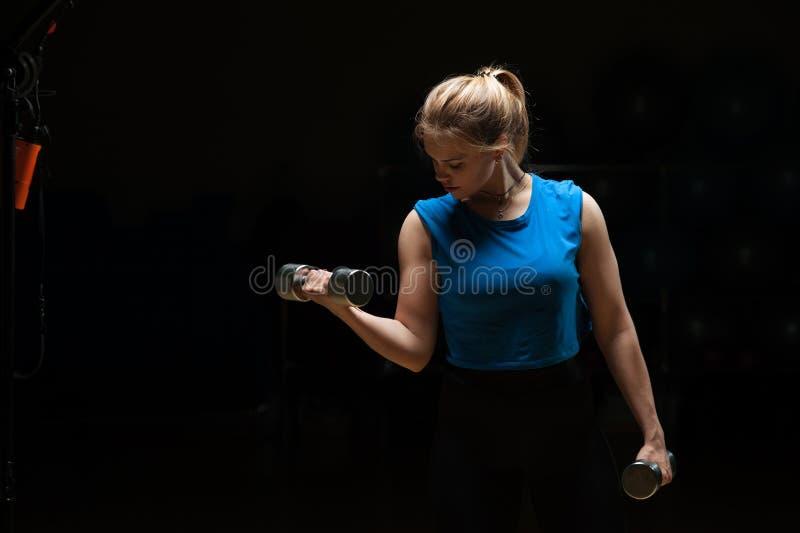 Dysponowana młoda kobieta ćwiczy z dumbbells fotografia royalty free