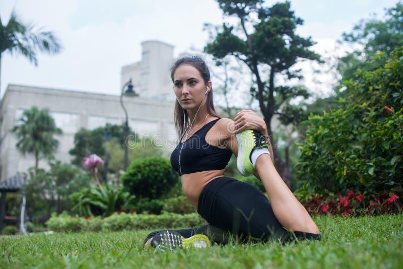 Dysponowana młoda kobieta siedzi na trawie w parku słuchająca ubierał w czarnym sportswear robi rozciągania ćwiczeniu dla nóg pod obraz stock