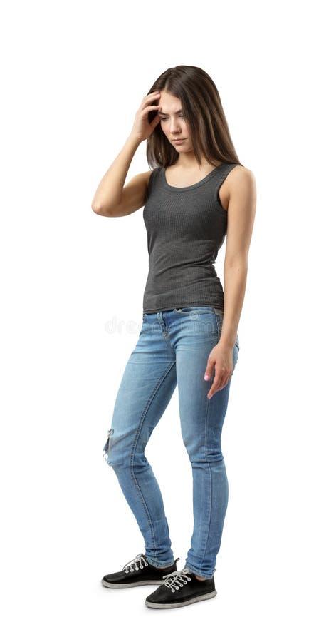 Dysponowana młoda kobieta stoi w półzwrocie z skołatanym spojrzeniem na dalej w szarym sleeveless wierzchołku, niebieskich dżinsa obrazy royalty free