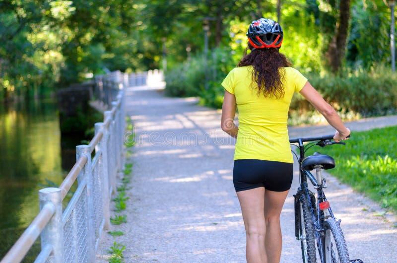 Dysponowana mięśniowa kobieta toczy jej bicykl outdoors obrazy stock