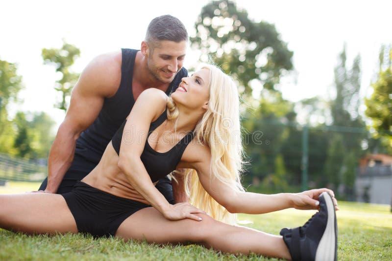 Dysponowana para robi ćwiczeniu plenerowemu na trawie obraz stock