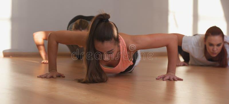 Dysponowane młode kobiety ćwiczy w sprawności fizycznej klasie fotografia royalty free