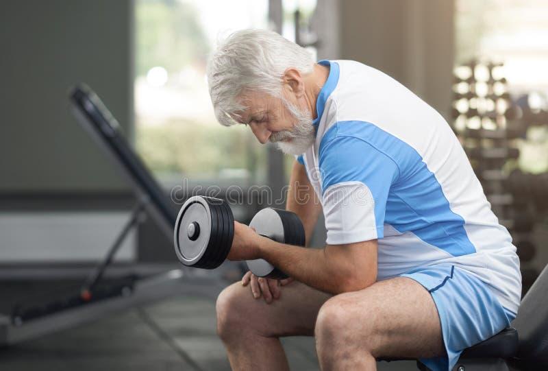 Dysponowane starsze osoby obsługują opracowywać z dumbbells w gym fotografia stock