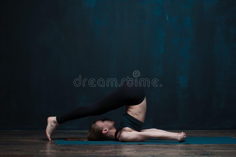 Dysponowanej dziewczyny joga ćwiczy asana przeciw zmrok ścianie fotografia royalty free