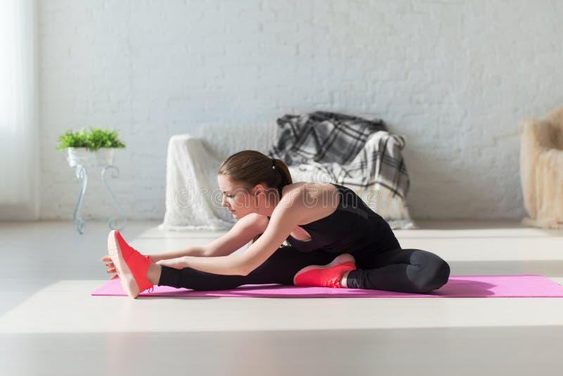 Dysponowanej kobiety ciała wysoka elastyczność rozciąga jej nogę zdjęcia royalty free