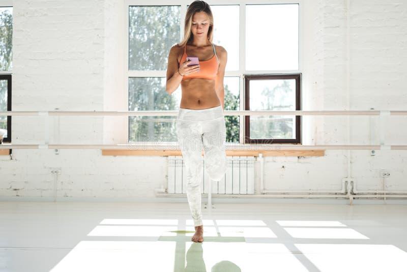 Dysponowany żeński athlet rozgrzewkowy up przed treningu i chwyta smartphone w ręka wczesnym poranku w pogodnym gym zdjęcia stock