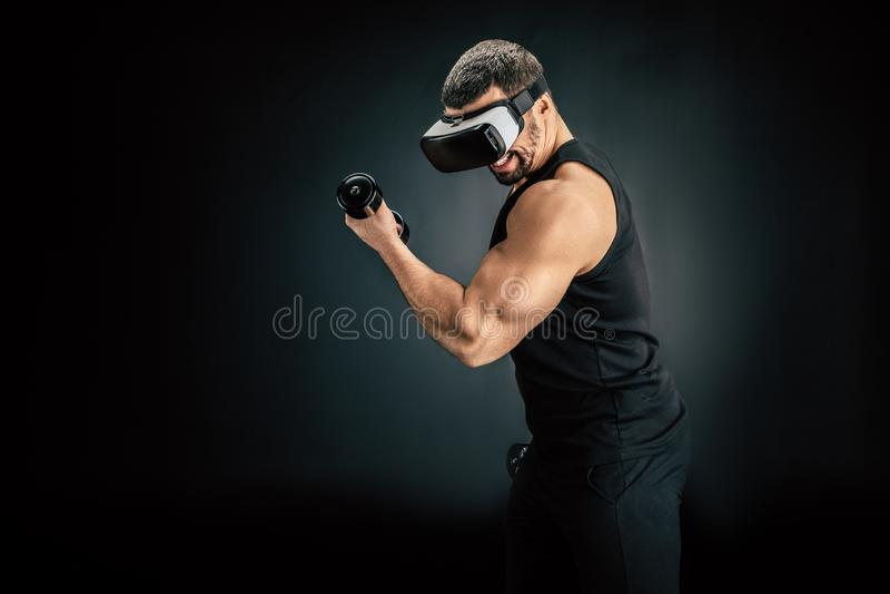 dysponowany mężczyzna ćwiczy z dumbbells w vr słuchawki fotografia stock