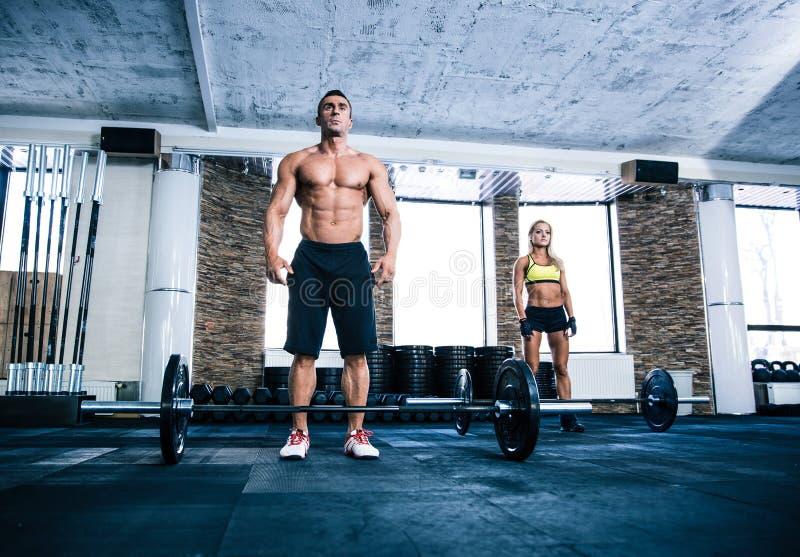 Dysponowany mężczyzna i kobiety trening przy gym fotografia stock