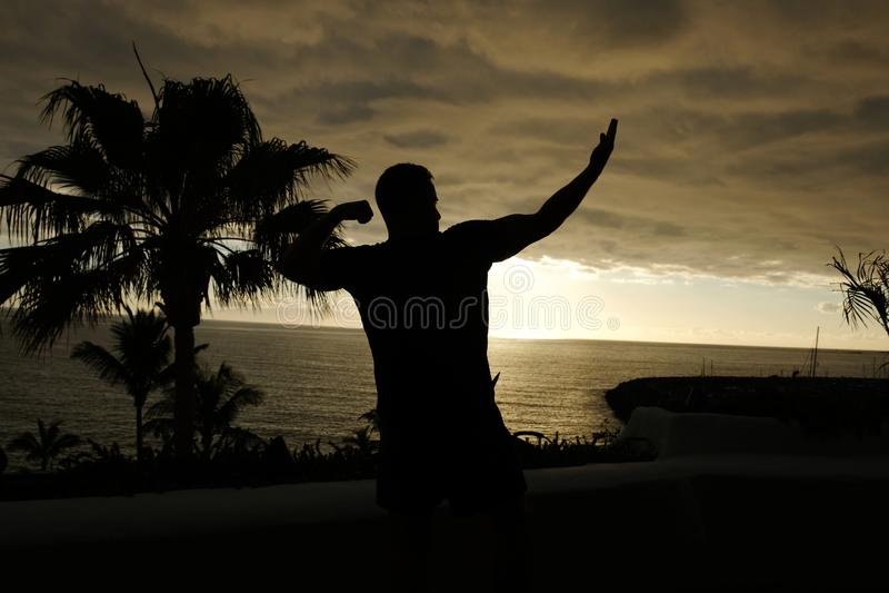 Dysponowany mężczyzna pozuje sylwetkę z zmierzchem nad oceanem obraz stock