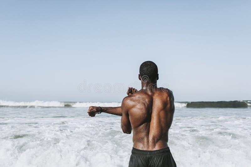 Dysponowany mężczyzna rozciąganie przy plażą zdjęcia stock