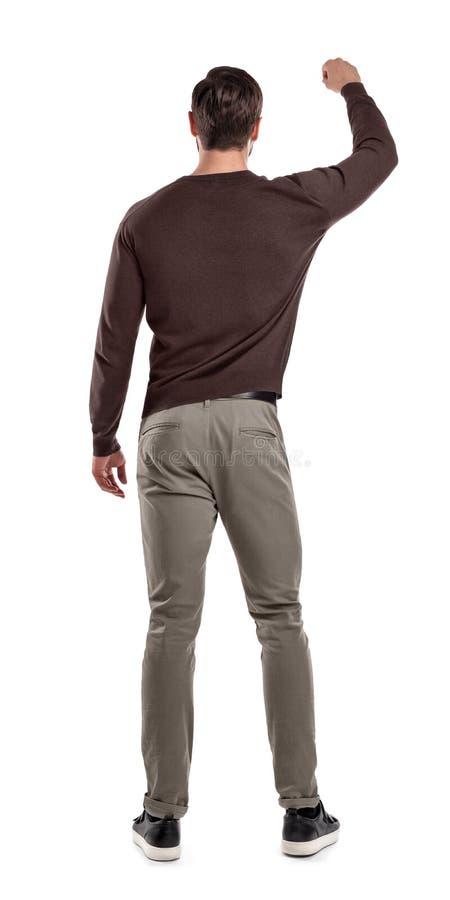 Dysponowany mężczyzna w przypadkowych pulowerów stojakach w tylnym widoku z jeden ręką podnoszącą w górę tak jakby trzymający coś obraz royalty free