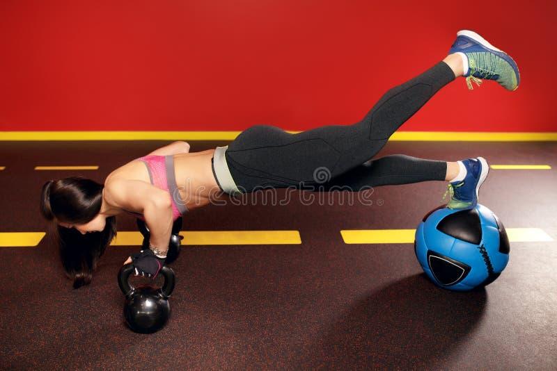 Dysponowany młoda kobieta trening w gym z kettlebell i medycyny piłką zdjęcie stock