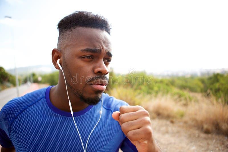 Dysponowany młodego człowieka bieg z słuchawkami zdjęcie royalty free