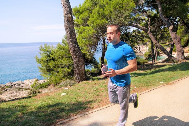 Dysponowany młody człowiek jogging na działającym śladzie wzdłuż seashore Rekreacyjna sprawności fizycznej atleta w sportswear ci obraz royalty free