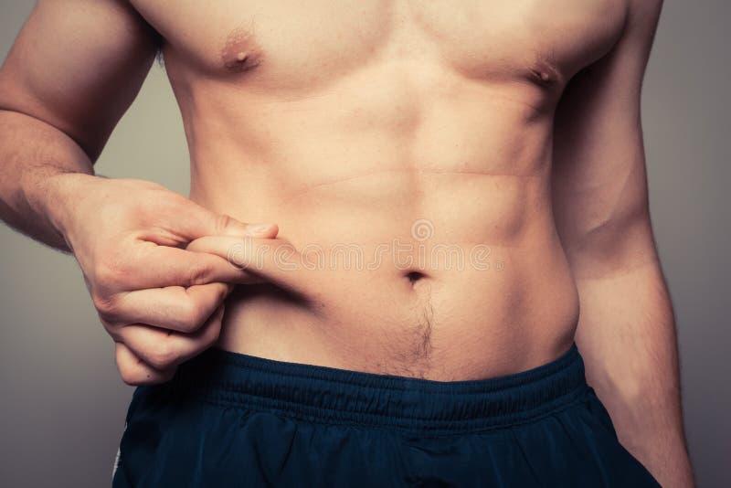 Dysponowany młody człowiek szczypa jego żołądek fotografia royalty free